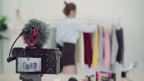 Asian fashion female blogger online influencer holding shopping bags and lots of clothes on clothes rack. Asian fashion female blogger online influencer holding stock video footage