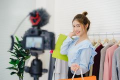 Female blogger online influencer holding shopping bags and lots of clothes on clothes rack for recording new fashion video. Asian fashion female blogger online royalty free stock photo