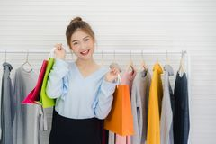 Female blogger online influencer holding shopping bags and lots of clothes on clothes rack for recording new fashion video. Asian fashion female blogger online stock photography