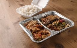 Asian fast food from delivery service in a foil container and ri royalty free stock images