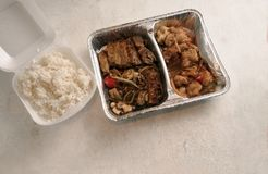 Asian fast food from delivery service in a foil container and ri stock photos