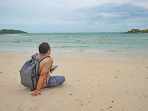Asian fat backpacker Sitting while see his mobile phone on the idyllic beach with beautiful Sky in vacation time royalty free stock images
