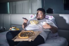 Asian fat man eating junk foods on the bed. Unhealthy lifestyle concept: Asian fat man eating junk foods while watching TV in bed before sleep stock photo