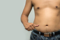 Asian fat man has cholesterol . He shows excess fat of the tummy Stock Images