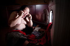 Asian fat man near washing machine. Asian fat man speak on the telephone near washing machine glowing inside stock photo