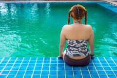Asian fat woman sitting at swimming pool Stock Images