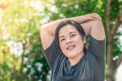 Asian Fat Woman Triceps Arm Stretching. Before running outdoors in the park stock image