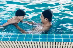 Asian father and baby lessons swimming pool in water. On summer time royalty free stock photos