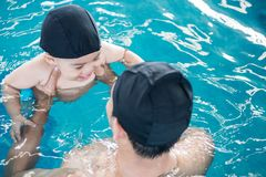 Asian father and baby lessons swimming pool in water. On summer time royalty free stock photo