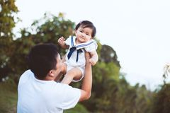 Asian father carrying his daughter up in the air stock photography