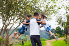 Asian father carrying two child girls and spinning around Stock Photos