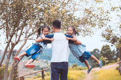 Asian father carrying two child girls and spinning around Royalty Free Stock Image
