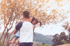 Asian father carrying two child girls and spinning around. With fun in the park in vintage color tone royalty free stock photography
