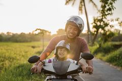 Asian father and child  ride motorcycle scooter stock photos