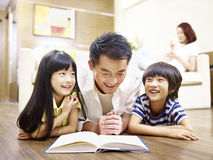 Asian father and children reading book together. Asian father and children lying on floor reading book with mother in the background Royalty Free Stock Images