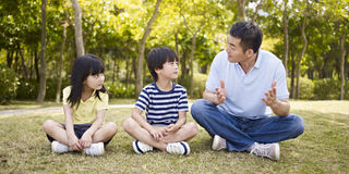 Asian father and children talking in park. Asian father and two children sitting on grass having an interesting conversation, outdoors in a park Stock Photo