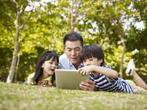 Asian father and children using tablet computer outdoors. Asian father and children lying on grass looking at tablet computer in a park Royalty Free Stock Photo