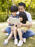 Asian father and children using tablet outdoors Royalty Free Stock Image