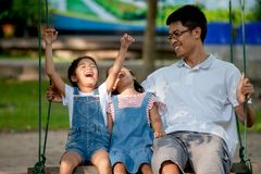 Asian father and daughter having fun to ride on swings together in playground royalty free stock photography