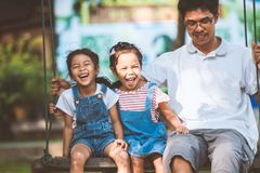 Asian father and daughter having fun to ride on swings together in playground royalty free stock image