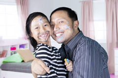 Asian father and daughter with painted face. Asian father and his daughter painted their faces while playing with crayons and looking at the camera Royalty Free Stock Images