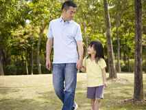 Asian father and daughter takes a walk in park. Asian father and elementary-age daughter enjoying a walk in nature Stock Photos