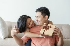 Asian father giving gift box for daughter the living room. Cute girl and father sitting on sofa be happy  in home. Asian father giving gift box for daughter  in stock photography