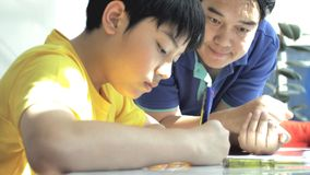 Asian father helping her son doing homework on white table stock photos