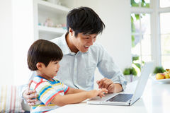 Asian Father Helping Son To Use Laptop At Home royalty free stock image