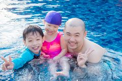 Father and his children in swimming pool. Asian father and his children in swimming pool stock image