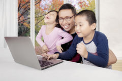 Asian father and his children using a laptop Royalty Free Stock Image