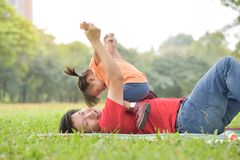 Asian father and his daughter playing together. Happy young Asian father and his daughter lying on the grass and playing together in nature at park outdoor royalty free stock photo