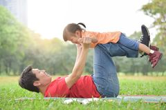 Asian father and his daughter playing together. Happy young Asian father and his daughter lying on the grass and playing together in nature at park outdoor royalty free stock image