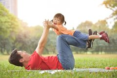 Asian father and his daughter playing together. stock photo