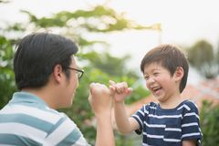 Asian father and his son making a pinkie promise. On nature background Stock Photos