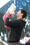 Asian father holding his baby. In mountains in winter time Royalty Free Stock Photos