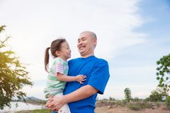 Father holding his daughter in park Stock Photography