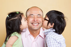 Asian father and kids. A shot of an Asian father kissed by his kids Royalty Free Stock Image