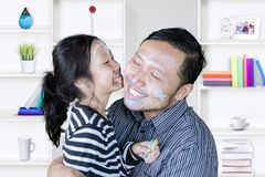 Asian father kissed by his daughter at home Royalty Free Stock Image