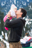 Asian father kissing his baby. Asian father holding and kissing his baby in mountains in winter time Royalty Free Stock Image