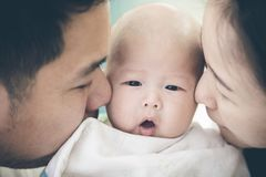 Asian family lovely moment . Asian father mother and baby son plays, kissing, lovely moment royalty free stock photo