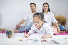 Asian father and mother looking daughter child painting color on. Book at home.Photo series of family, kids and happy people concept Stock Photography