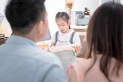 Asian father and mother looking daughter child painting. With watercolor on the easel at home.Photo series of family, kids and happy people concept Royalty Free Stock Photography
