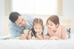Asian father and mother teaching her daughter child. Happy family in the bedroom,Asian father and mother teaching her daughter child to studying at home.Photo Royalty Free Stock Photography