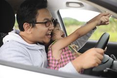 Asian Father Playing with His Daughter in Car. Portrait of Asian father playing with his little baby girl daughter in car sunlight daddy outdoors bonding sunset stock photography