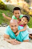 Father playing with his kids on the beach. Asian father playing with his kids on the beach Royalty Free Stock Images