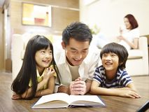 Asian father reading book telling story to two children. Asian father and two children lying on front on floor reading book while mother relaxing in the Stock Photos