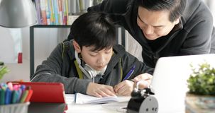 Asian Father and son doing homework at home. Asian Father and son doing homework on the table in the living room stock images