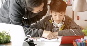 Asian Father and son doing homework at home. Asian Father and son doing homework on the table in the living room stock photography