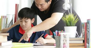 Asian Father and son doing homework at home. Asian Father and son doing homework on the table in the living room royalty free stock image